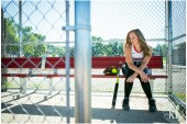 An editorial shot of a high school senior girl softball player in the dugout.