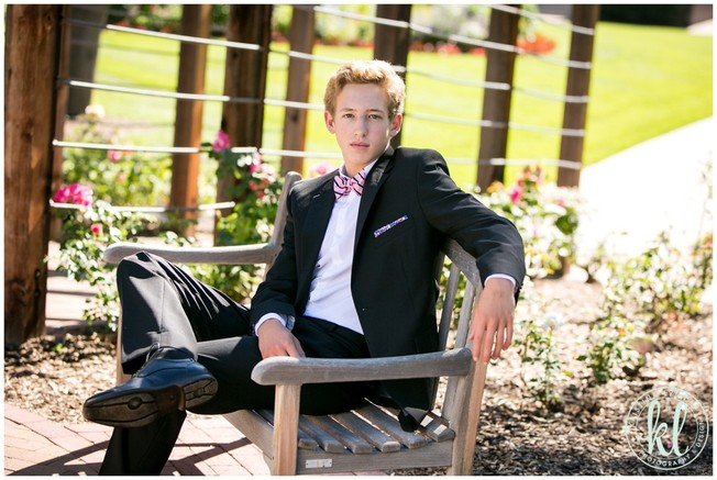 High school senior boy dressed in a sophisticated black suit | Image by Kristina Lynn Photography & Design.