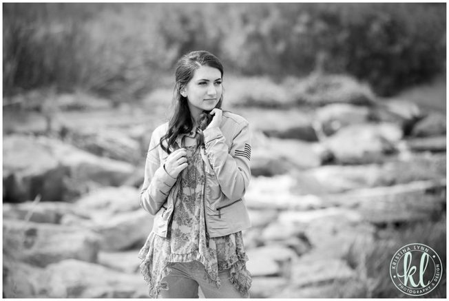 Editorial style black and white image of a girl standing in a rocky river bed.