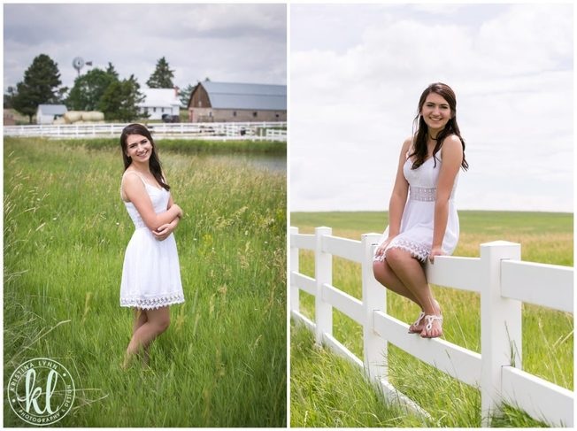A girl in a white dress sitting on a white picket fence on a farm.