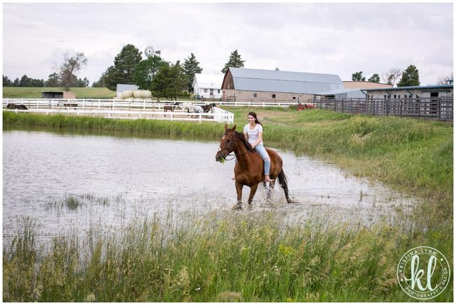 A young girl riding her horse through a water hole on a farm in rural Minnesota