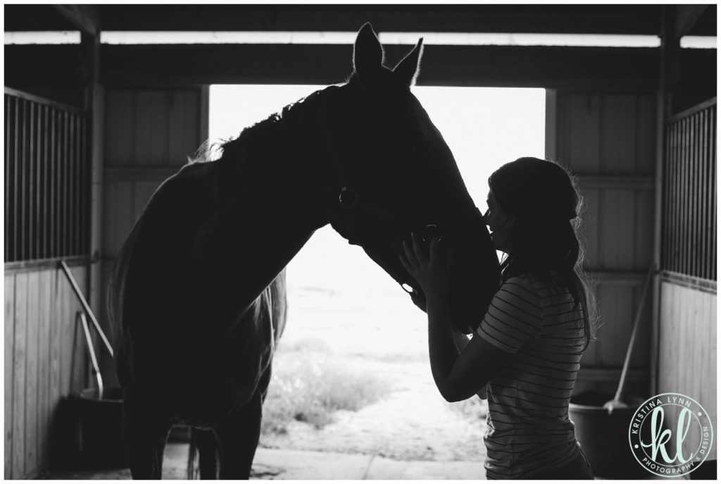 Silhouette photo of a girl kissing her horse in a barn in Parker Colorado.