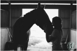 Silhouette photo of a girl kissing her horse in a horse barn in Parker Colorado.